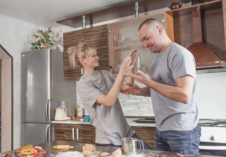 A young, newly married, happy, carefree couple in love has fun making flour cookies together in the kitchen. The concept of happiness, home fun, family, cooking, love.