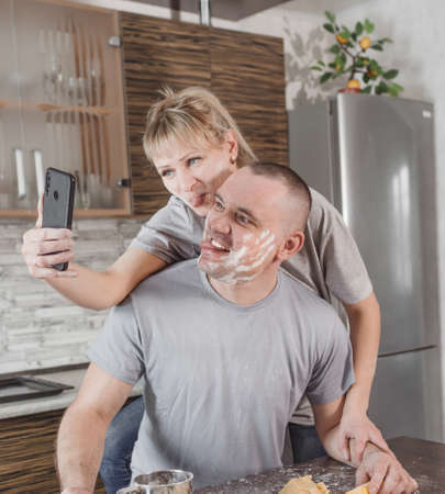 happy married couple taking photos of each other on the phone showing their tongue smeared in flour while cooking in the kitchen