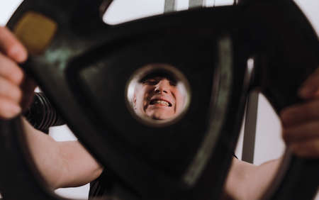 tense and full of pain, the face of a man lifting a weight in a fitness club. sports training healthy lifestyle. Standard-Bild