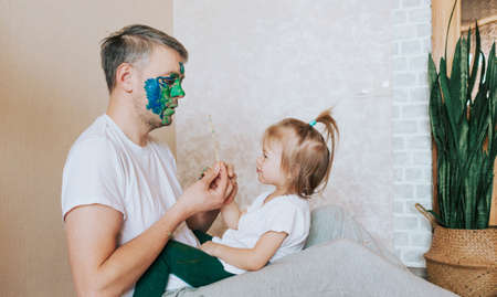 a little girl is sitting on her father's lap painting his face with a brush of oil paints.