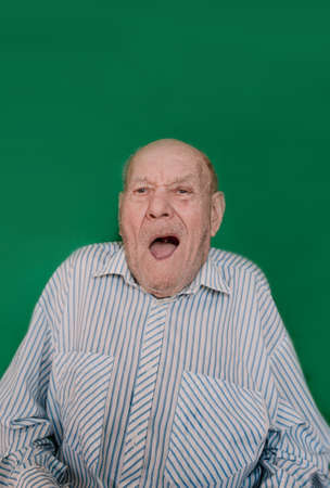 a crazy old man makes faces and grimaces against an isolated green background. chromakey