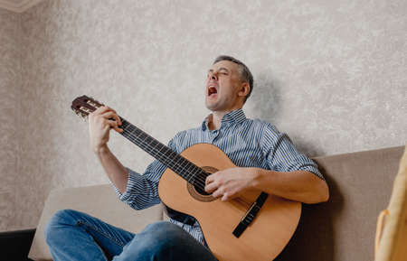 A young man plays the guitar sitting on a sofa in a bright living room. A musical instrument for the concept of leisure or hobby. home entertainment