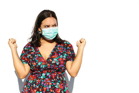 Latin and natural young woman wearing A Face Mask on a white background. She has a pissed off gesture