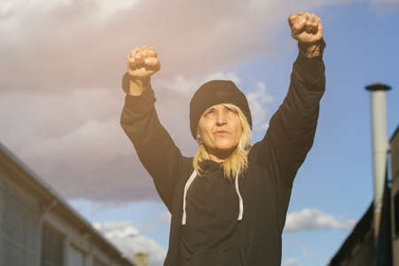 Boxer woman wearing a wool cap, looking up with her arms raised on a factory and sky background of the street. Real women concept. Stock Photo