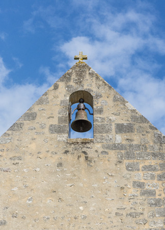 theology: Bell in Church with blue sky and old stone wall. Stock Photo