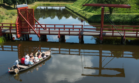 drawbridge: Boat with tourist and a guide sailing to a drawbridge at the fortress of Bourtange.