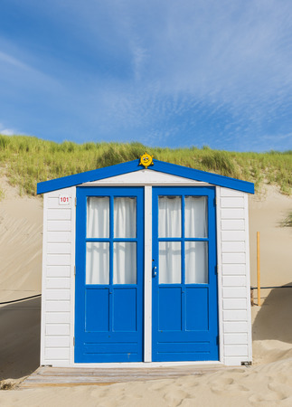 White with blue doors and  cabin on the beach on the isle of Texel.