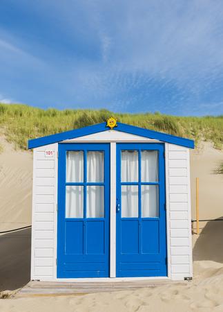 Wit met blauwe deuren en cabine op het strand op het eiland Texel.