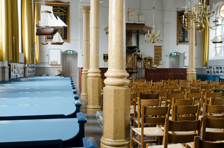 pews: Interior of the protestant church of Marken with blue pews and wooden chairs. At the ceiling there are models of boats and chandeliers.