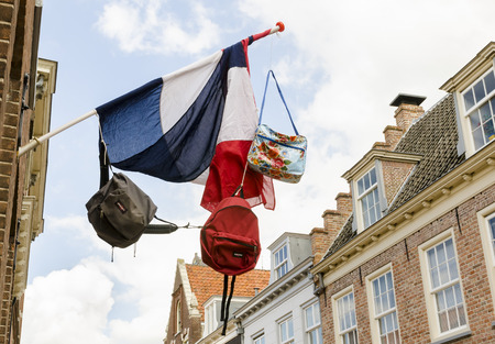 Dutch flag with three bags on it, and in the background old houses of the town of Wijk bij Duurstede.