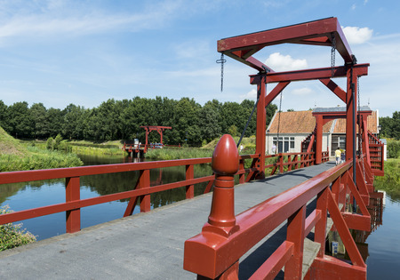 The red drawbrifge to the entrance of fortress Bourtange in the province of Groningen photo