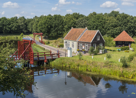Entrance of the pittoresque town of Bourtange with a smal house and two red bridges.