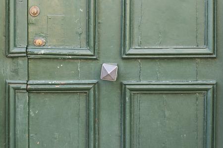 green door: Old green door with door handle in Nevers in France.