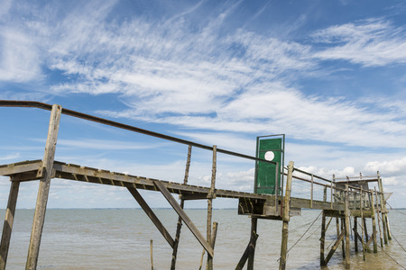 gironde: Wooden jetty for fishing in the Gironde Medoc France with blue sky and white clouds.