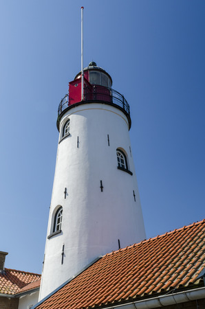 flevoland: White and red lighthouse (tower) of Urk with in front some houses , Flevoland, The Netherlands