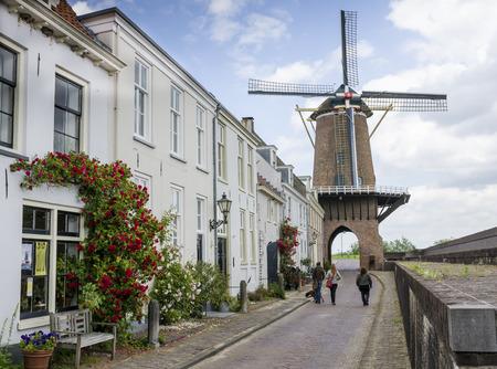 Molen Rijn en Lek in de gemeente Wijk bij Duurstede met een baksteen stoep straat en rode rozen. Stockfoto - 36997903