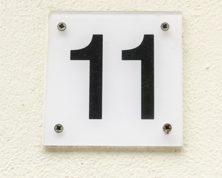 11: Sign of house number 11 in black karakters on a white yellowish wall. Stock Photo
