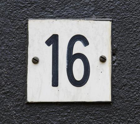mur noir: Signe de la maison num�ro 16 dans karakters noires sur un mur noir.