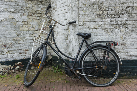underprivileged: Old black bicycle against a dirty white brick wall. Stock Photo