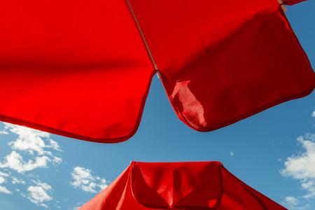 Rode parasol tegen een blauwe hemel.