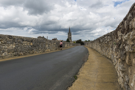 saint emilion: Road, Church and stroller on a black road in Saint -Emilion with dark sky and clouds.
