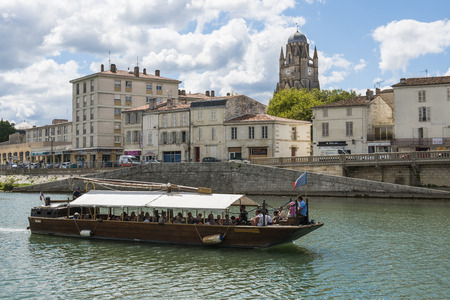 middle ages boat: Saintes in France with boat on the river and clouds in the blue sky. Stock Photo