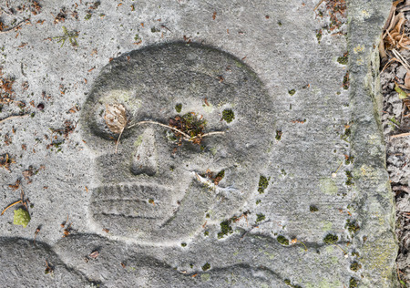 theology: Skull in a gravestone on a graveyard in Usquert in the province of Groningen.