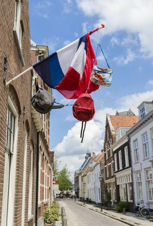 Straat in Wijk bij Duurstede met oude huizen en de Nederlandse vlag met drie tassen.