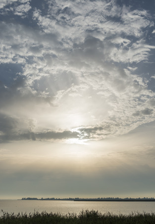 sunbeams: Sunbeams and dark clouds above the national park Lauwersmeer. Stock Photo
