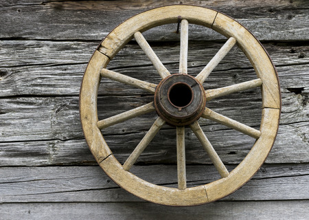 Spoked wooden wheel on the wall of a logcabin in Austria. Stock Photo