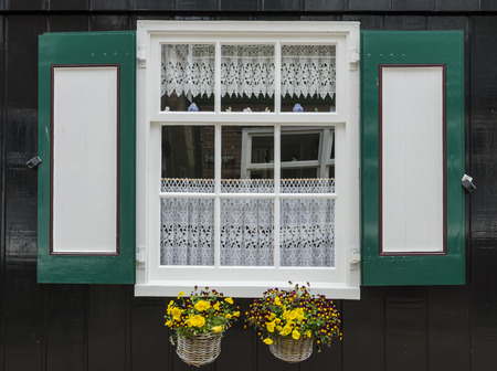 marken: Window in a black wooden house with green and red shutters and two small baskets with flowers in the town of Marken, the Netherlands. Stock Photo