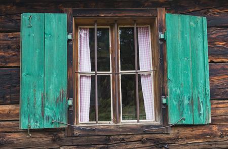 saalfelden: Window with green shutters in an old logcabin in Austria. Stock Photo