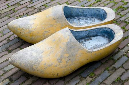 wooden shoes: Big Dutch wooden shoes on a brick pavement.