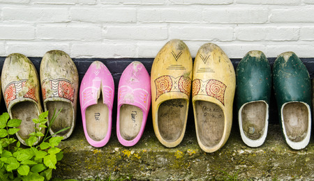 wooden shoes: Several Dutch wooden shoes against a black and white wall. Stock Photo
