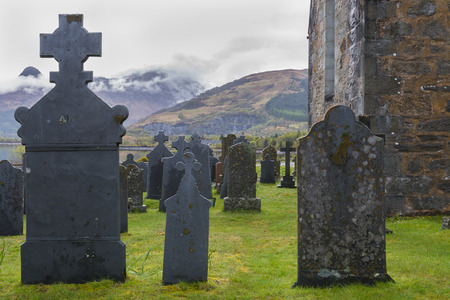 spooky graveyard: Graveyard Ballachulish with Chapel and gravestone with mountains. Stock Photo