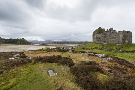Castle Tioram in the Highlands of Scotland with hills and sea.