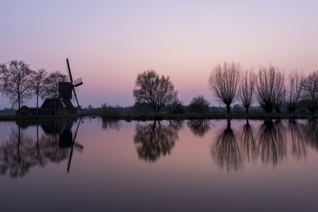 drakes: Mill at Woerdens Verlaat after sunset near the Kromme Mijdrecht and with refelection in the water. Stock Photo