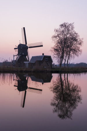 Mill at Woerdens Verlaat after sunset near the Kromme Mijdrecht and with refelection in the water. 스톡 콘텐츠