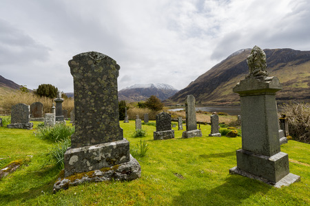 graveyard: Graveyard in Ault A39Gruinn in the Highlands of Scotland with lake snow and piles of stone image Daan Kloeg Commee Stock Photo
