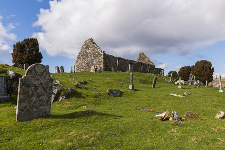 graveyard: Graveyard on the Isle of Skye in the Highlands of Scotland with lake, snow and piles of stone.