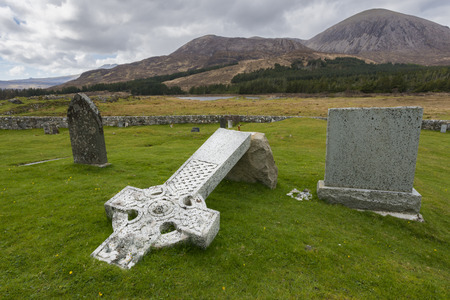 burried: Graveyard on the Isle of Skye in the Highlands of Scotland with lake, snow and piles of stone.