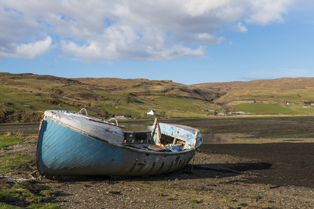 beached: Old blue shipwreck at the coastline on the Isle of Skye in Scotland.