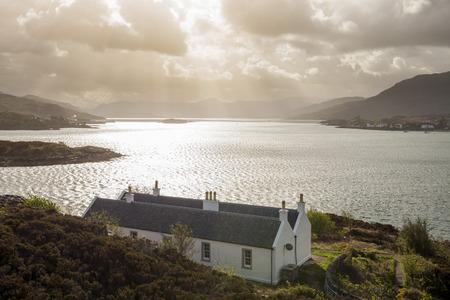 sunbeams: Houses near the bridge of Isle of Skey with dark clouds and sunbeams.