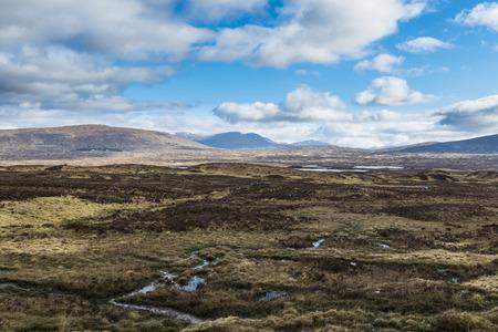 Typische Schotse Hooglanden met bergen, heuvels, kreek, hetaher en wolken in de lucht.