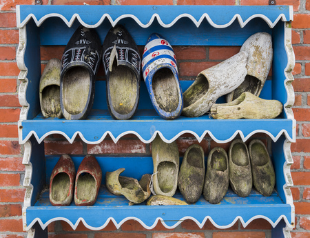 klompen: Wierum, The Netherlands - April 18, 2016: Several old wooden shoes on a blue painted wooden rack against a brick wall in Friesland, The Netherlands. Editorial