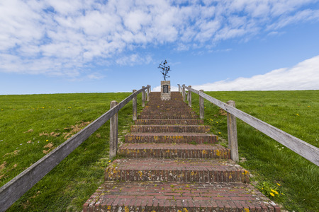 friesland: Wierum, The Netherlands - April 18, 2016: Statue for the dead fishermen on the Waddensea dike with stone stairs at Wierum in Friesland.