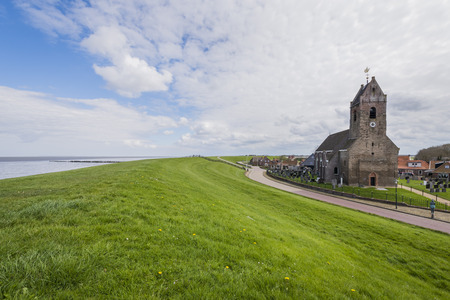friesland: Wierum, The Netherlands - April 18, 2016: Church of Wierum with Waddensea dike in Friesland in the Netherlands.