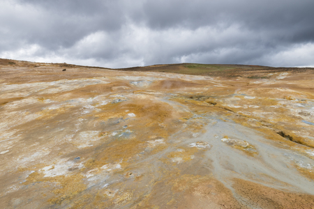 famous industries: Geothermal landscape Krafla on Iceland with red dirt, steam and a hot water stream down a hill.