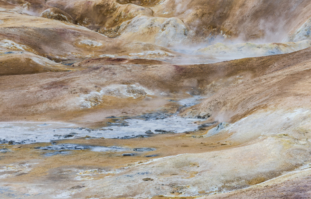 hot water geothermal: Geothermal landscape Krafla on Iceland with red dirt, a hot water stream, steam and tourists.