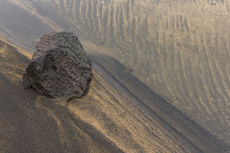 Lava Rock and Sand patterns of yellow and black lava and volcanic sand at a beach in the water. Stock Photo